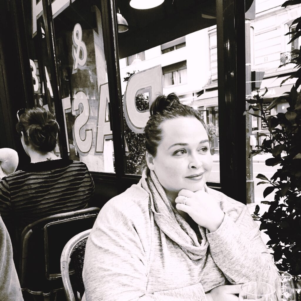 Black and white photo of a woman at a Parisian Cafe looking into the distance