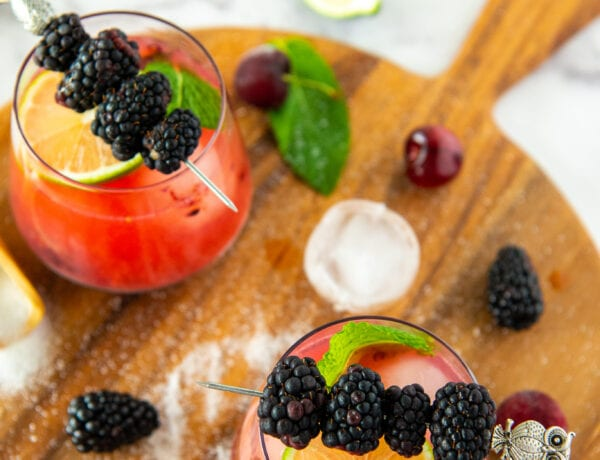 Glasses filled with Blackberry Margaritas topped with a skewer of Blackberries