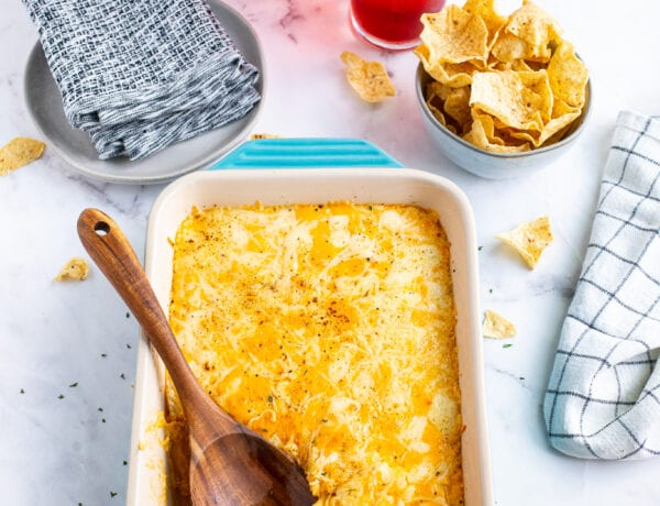 Buffalo Chicken Dip in a blue baking dish with a wooden spoon surrounded by a bowl of chips and drinks