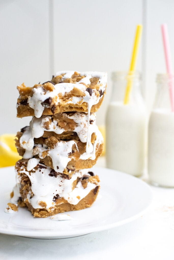 Stack of Fluffernutter Cookie Bars with two jars of milk in the background