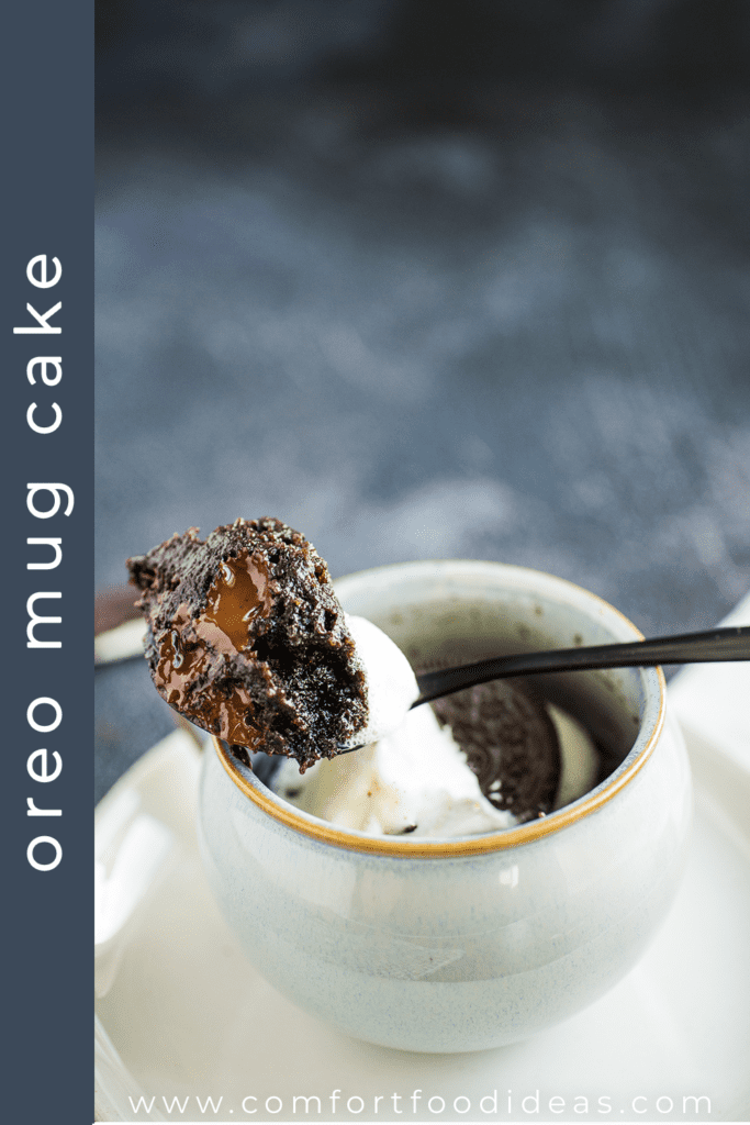 Bite of Oreo Mug Cake in a spoon resting on a coffee mug