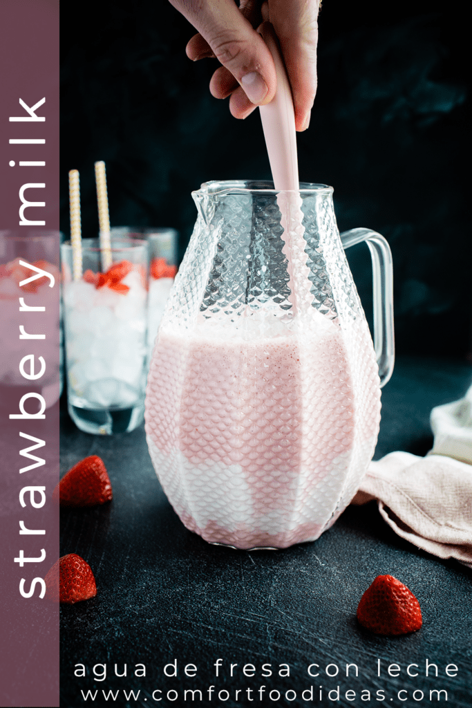 Someone stirring pitcher of Strawberry Milk
