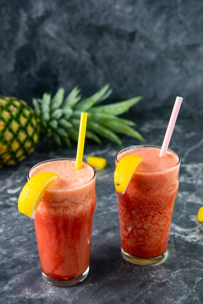 Two glasses of Frozen Strawberry Pineapple Lemonade on a dark surface