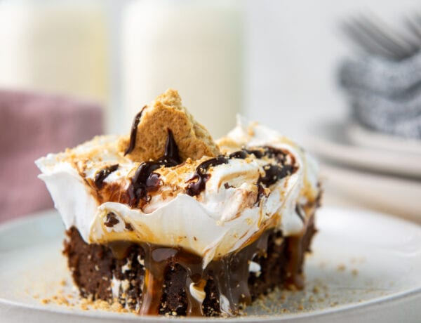 One piece of S'mores Brownie with caramel drizzle on a light plate and white concrete backdrop
