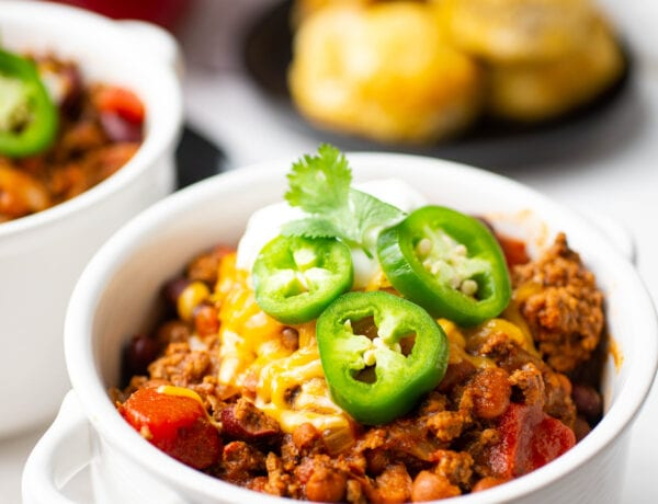 White bowl of chili topped with jalapeños