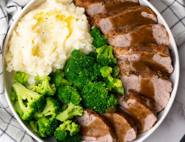 Apple Cider Pork Medallions with veggies in a white serving dish